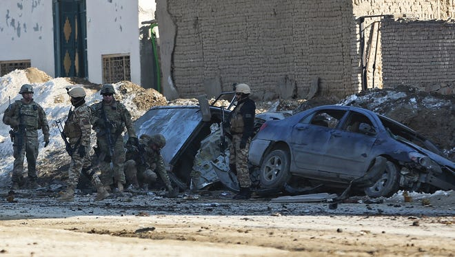 U.S. soldiers and Afghan security forces search the site of a suicide bombing that struck near a NATO convoy in the Afghan capital Kabul on Feb. 10, 2014.