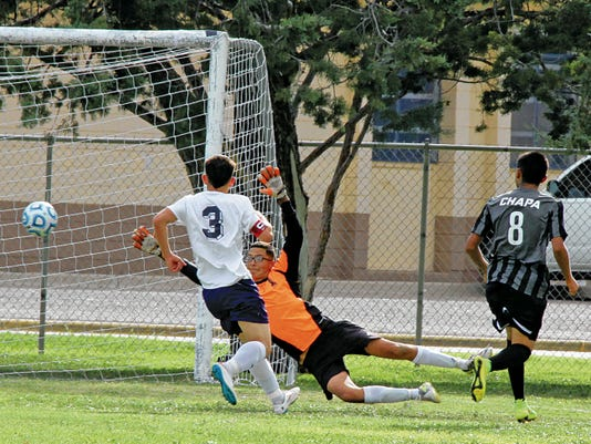 Wildcats freshman goalkeeper Juan Nevarez stretches for a Chaparral shot on goal while junior Captain Francisco Loya (3) trails the play during Deming's 2-1 loss to the Chaparral Lobos on Tuesday at the Deming High Soccer Field.