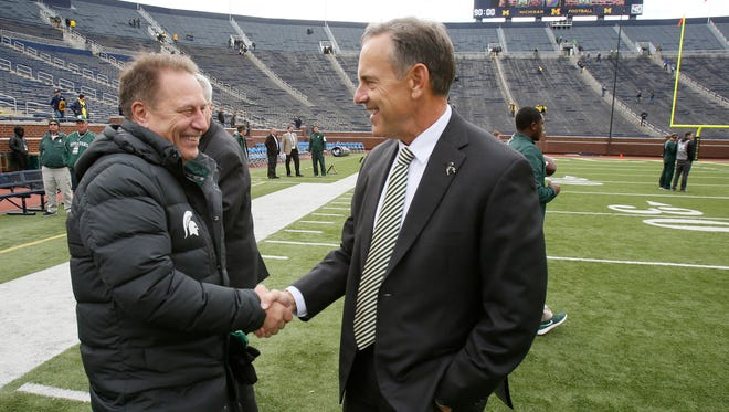 Michigan State basketball coach Tom Izzo greets football coach head coach Mark Dantonio on the field at Michigan Stadium before their football game against Michigan on Saturday, October 17, 2015, in Ann Arbor. Julian H. Gonzalez/Detroit Free Press