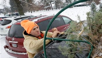 Howell Tree Farm employee Chris Allen loads a Christmas tree on top of a customer's car, Wednesday in Cumming, Iowa. The Christmas tree likely will cost a little more this year, and growers say it's about time. Six years of decreased demand and low prices put many growers out of business and those who hung on are just relieved they survived.