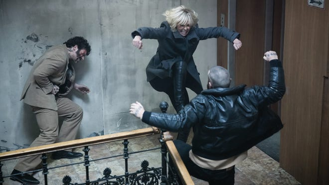 """Charlize Theron (center) plays an undercover agent who, as the Cold War winds down, is sent to Berlin to find out who's killing Britain's top spies in """"Atomic Blonde."""""""