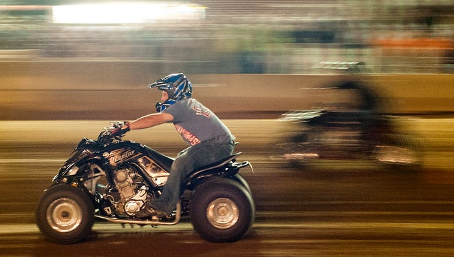 Racers lean back on their four wheelers and run all out in front of a crowd on the track at the Fairfield County Fairgrounds on Tuesday night during the KOI Drag Racing at the Fairfield County Fair.