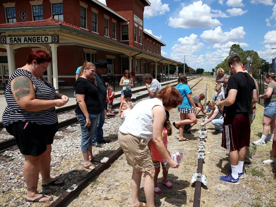 """Participants place eggs to """"fry"""" on the railroad tracks"""