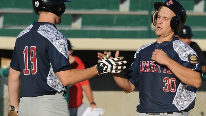 Jeremy Griggs congrats Joe House as the pair cross the plate to score for Lafayette Post 11 in American Legion play Tuesday night at Loeb Stadium.