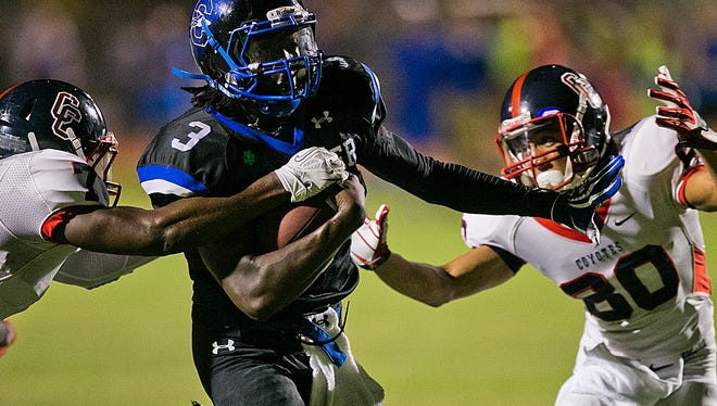 Chandler's Bryce Perkins eludes Peoria Centennial's Amare Burks, left, and Justin Ackie in a high school football game on Thursday,Aug. 29, 2013 in Chandler.