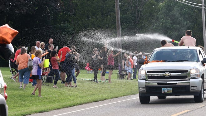 2020 Marlington graduates spray water on family and friends watching a parade featuring the Class of 2020. The event included vehicles from the fire departments from the three townships that make up the Marlington Local School District.