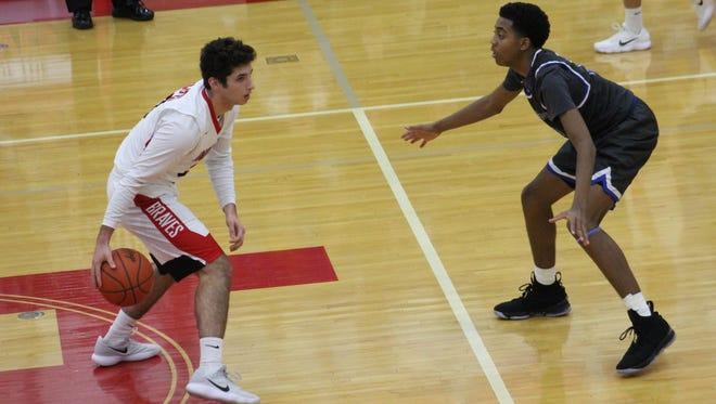 Indian Hill senior Marco Fiore sets up the Braves offense while being guarded by Wyoming freshman Isaiah Walker Jan. 24.