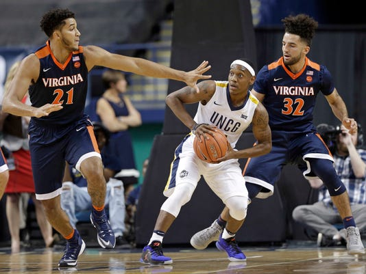 """FILE - In this Nov. 11, 2016, file photo, UNC-Greensboro's Diante Baldwin, center, is trapped by Virginia's Isaiah Wilkins, left, and London Perrantes, right, in the first half of an NCAA college basketball game in Greensboro, N.C. Four days after Syracuse head coach Jim Boeheim angered an entire city by saying there was """"no value"""" in the Atlantic Coast Conference holding its postseason tournament in Greensboro, N.C., the Orange were matched up on Sunday, March 12, 2017, against UNC Greensboro in the first round of the National Invitation Tournament. (AP Photo/Chuck Burton, File)"""
