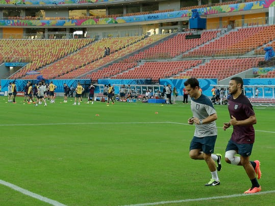 England's Alex Oxlade-Chamberlain, right, who is recovering from a knee injury, trains with a coach away from the rest of the squad during a training session of the England national soccer team at the Arena da Amazonia in Manaus, Brazil, Friday, June 13, 2014.  England play Italy in group D of the 2014 soccer World Cup at the stadium on Saturday. (AP Photo/Themba Hadebe)