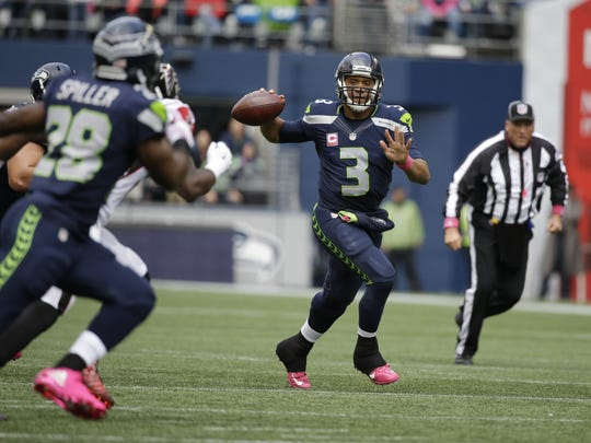 Seattle Seahawks quarterback Russell Wilson (3) throws a 24-yard pass to running back C.J. Spiller (28), in the first half of Sunday's game at the Atlanta Falcons.