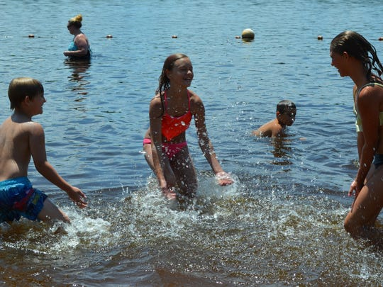 Carlos Rosa, 6, Vaeda Rosa, 12 and Adriana Fricano, 12, all of Newfield splash in the water at Parvin Lake on Saturday during the inaugural Christmas in July event.