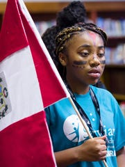 Lanrya LaRue, age 12, holds a Peruvian flag at a summer program with an around-the-world exhibit at Serviam Girls Academy in New Castle on Thursday.