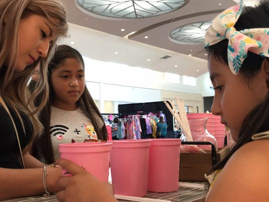 Brianna Avalos, 6, prepares to hand a customer a cup of her homemade lemonade at her lemonade stand in front of the Kendra Scott store at La Palmera mall on Saturday, May 12, 2018.
