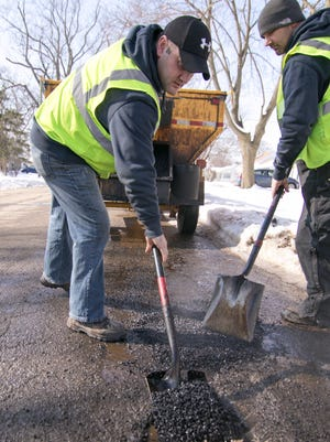 Brighton Department of Public Works operators Shane Basch, left, and Steve Brown patch potholes near State and Fifth Streets in the city of Brighton Wednesday, Feb. 14, 2018.