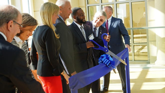 Carlos Cannon, a student in the Year Up program, a national non-profit that empowers urban youth through education, is surrounded by officials during a ribbon cutting ceremony for the program at the Community Education Building Tuesday morning.