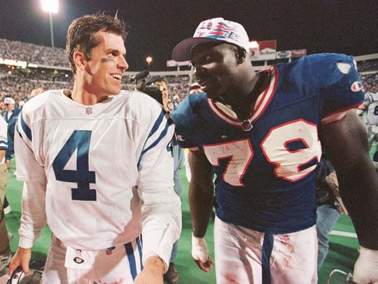 Bills DE Bruce Smith shares a lighter moment with Colts QB Jim Harbaugh after a 1996 game.