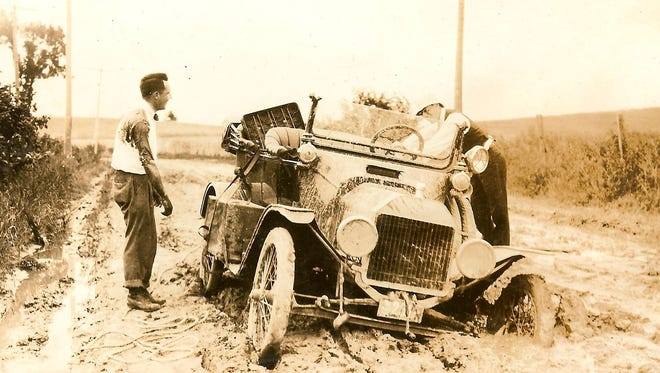"""Day 3 --June 19, 1915 --Vandalia, IL to St. Louis, MO (85 miles). Ford Model T Touring, Horace J. Caulkins Jr. (left) and Thomas C. Whitehead (right).  Edsel's diary note: """"became stuck in mud 18 miles east of St. Louis. Tackle and block failed to move it."""""""