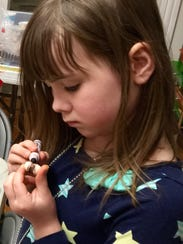 Annalyn Dakin, 8, carefully colors one of her gnome