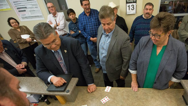 """Enrique """"Kiki"""" Vigil, left, Carlos H. Preciado, center, and Kim Stewart all Democratic candidates for sheriff look over the cards they pulled during the ballot position draw. Tuesday March 13, 2018."""