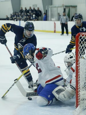 Fairport's Jordan Falk and goalie Michael Layer defend against Brighton/Honeoye Falls-Lima's Ryan Kane in the first period at Thomas Creek Ice Arena. Falk scored later for the Red Raiders.
