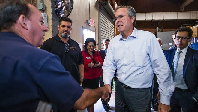 Gov. Jeb Bush, right, greets Four Peak Brewery co-owner Jim Scussel, left, at a May event in Tempe. Bush's Arizona supporters include former Vice President Dan Quayle and former Gov. Fife Symington.