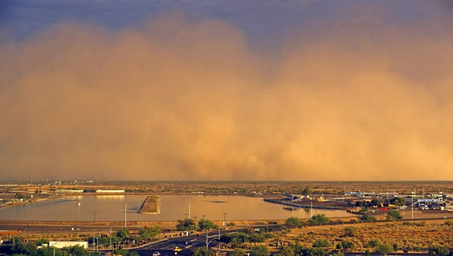 A dust storm moves over Firebird Lake Tuesday, July 19, 2016 in Chandler, Ariz..