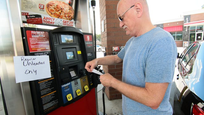 Dave Russell of Williamston looks at his receipt after filling his car with regular unleaded gas at the QuikTrip station on Greenville Street in Anderson.
