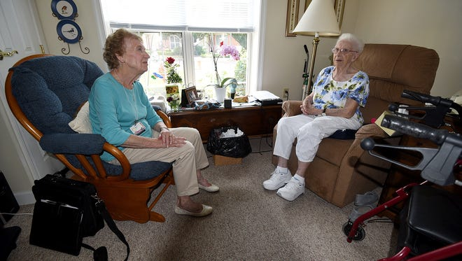 Shirley Barry and Mary Frisbee converse Monday afternoon at the window of Frisbee's residence at Wedgewood Estates.