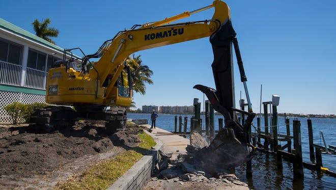 Workers for Williamson & Sons Marine Construction, Inc. begin the demolition process of a damaged sea wall at a house on Flamingo Drive in Cape Coral near the Cape Coral Yacht Club. The sea wall structure, which was in need of repairs prior to Hurricane Irma, received additional damage from the hurricane last year.