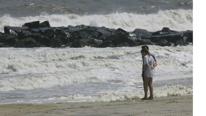 A couple watches the waves roll onto the Spring Lake beach in 2016.