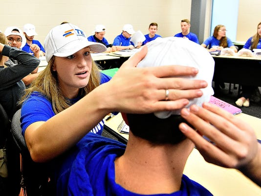 Spring Grove's Katie Garner, front left, helps Tesla team member Rory Trout, front right, to adjust his hat as students prepare to participate in a teleconference with NASA, kicking off the 2016 NASA Student Launch Initiative (SLI) program at Spring Grove High School in Spring Grove, Pa. on Wednesday, Oct. 7, 2015. There are 14 high school teams involved in the program from across the country, two of which are from Spring Grove, and are the only Pennsylvania teams to have been selected. The teams will need to raise 25,000 dollars to fund their projects, through multiple fundraising events.  Dawn J. Sagert - dsagert@yorkdispatch.com
