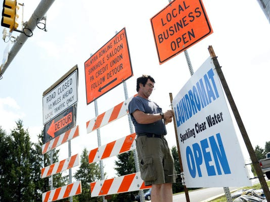 Kurt Yordy owner of the Wash Basket Laundromat and Sparkling Clean Water, hangs up a sign on Wednesday to let patrons know his businesses remain open despite work to bypass a sinkhole on Route 422 in North Londonderry Township.
