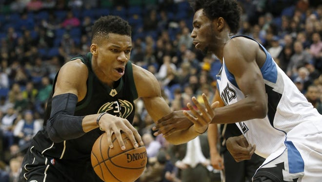 Milwaukee Bucks forward Giannis Antetokounmpo, left, of Greece, drives against Minnesota Timberwolves guard Andrew Wiggins, right, during the second half of an NBA basketball game in Minneapolis on Jan. 2. The Bucks won 95-85.