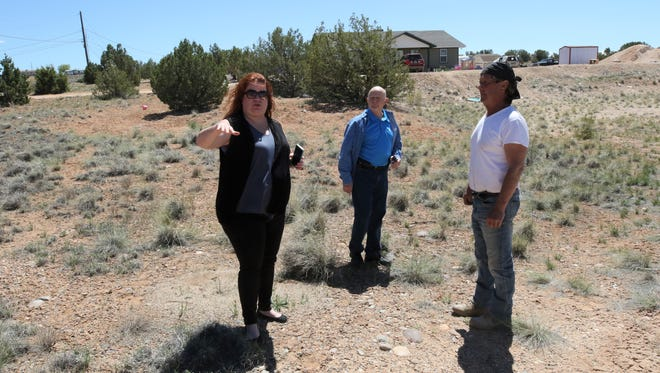 Hope Tyler, left, Frank Hayes and Greg Anderson of Tres Rios Habitat for Humanity, survey a lot on Crouch Mesa where the organization's latest home is being built.