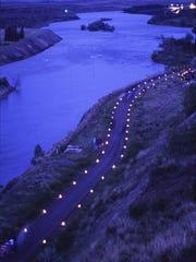 Candles light the River's Edge Trail during the annual Luminaria Walk.