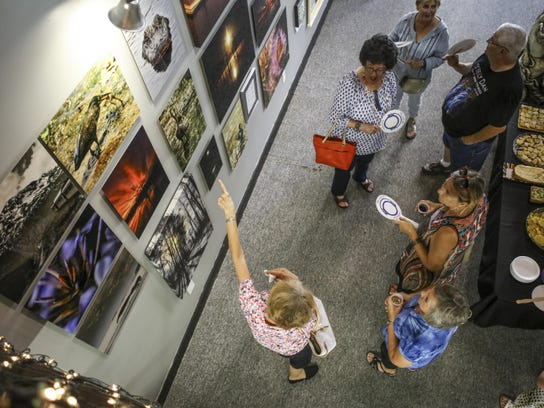 Visitors look at art during an August Downtown Gallery