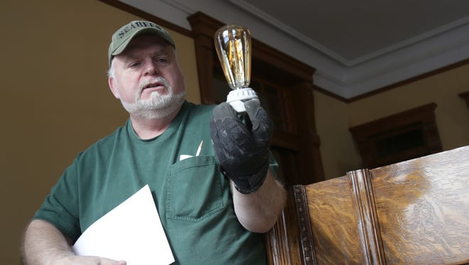 Bill Sample shows a reproduction vintage lightbulb that he'll use in the cabinet that monitors power to the electric chair at an exhibit for the Ohio State Reformatory.