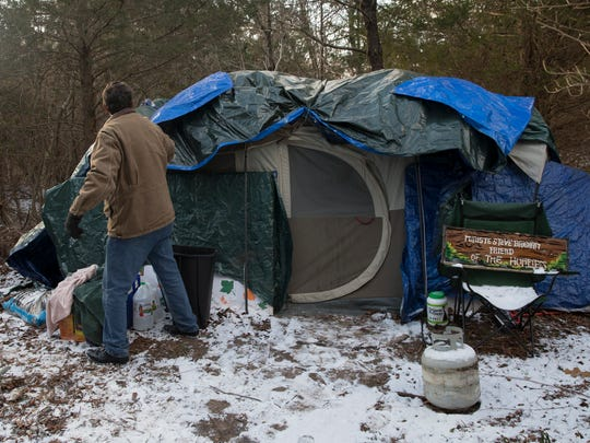 Reverand Steve makes adjustments to the additional plastic layers of his tent as he check all the structures  in the camp during the latest windy front that brought in frigid weather. So far, all the tents are holding up.