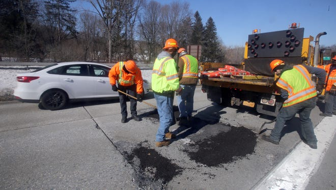 A New York state Department of Transportation crew fills potholes on the northbound Sprain Brook Parkway in Hawthorne, Feb. 14, 2017.