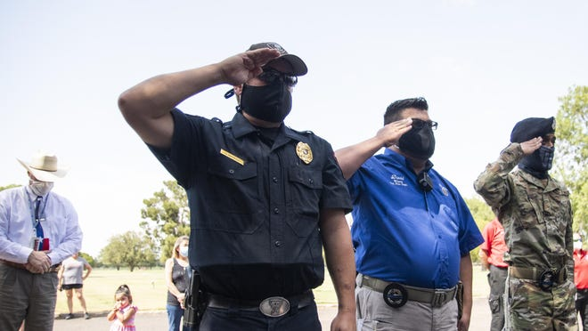 Law enforcement from multiple area departments salute the casket of Lynn County Sheriff Abraham Vega at the Resthaven Funeral Home in Lubbock, Texas, on Wednesday, July 15, 2020. Sheriff Vega died on Saturday, July 11, 2020 due to complications from COVID-19.