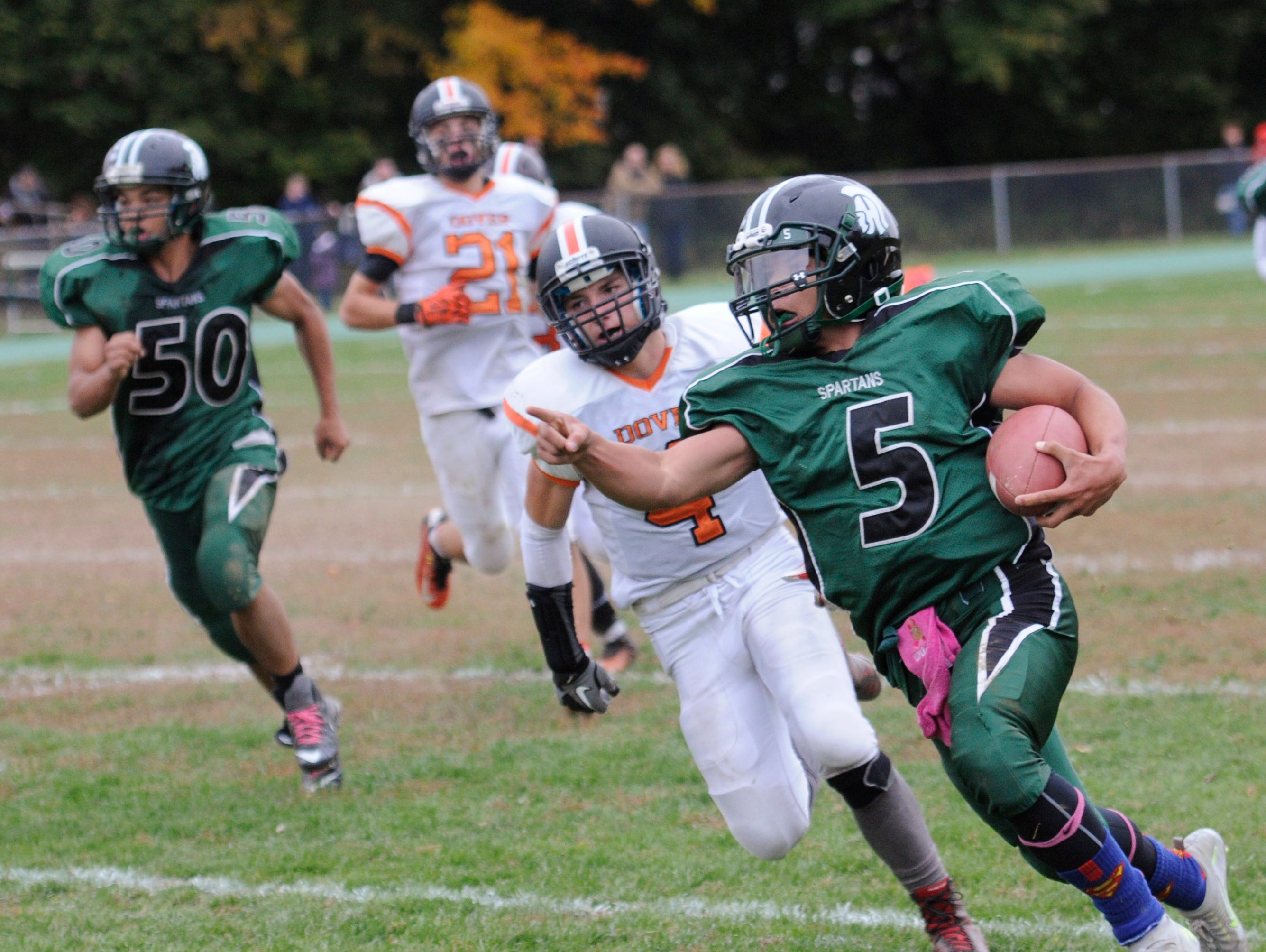 Spackenkill High School's Camron Abalos points out a tackler as Dover's Colin Belanger pursues during an Oct. 24, 2015 game in Poughkeepsie.
