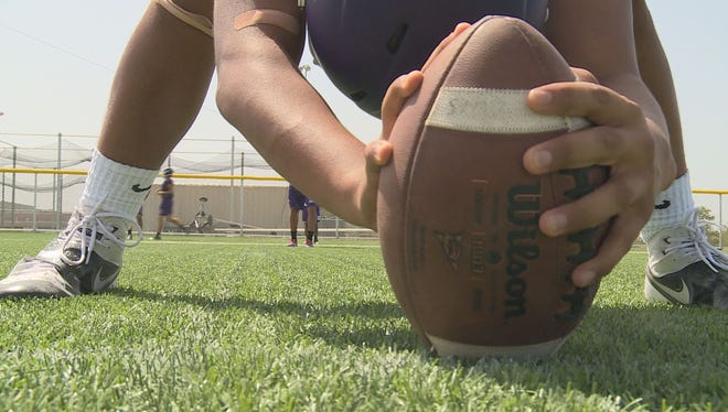 A San Marcos High School football player prepares to snap the ball