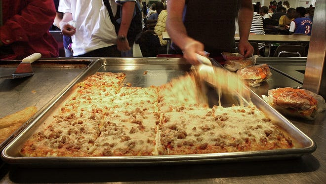 Students dish up pizza in one of the hot food lines in the cafeteria at Germantown High School.