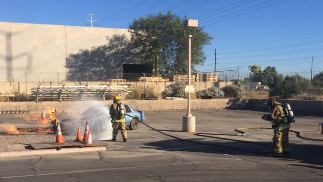 Firefighters work to extinguish a natural gas fire as part of a training exercise in Tempe on Nov. 24, 2014.
