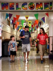 James Christian Price, 7, and his father James Paul Price walk through the halls of Wilson Elementary School with Jordan Dykstra, a 2nd-grade teacher, during a community block party at the school Tuesday, Aug. 30, 2016, in Neenah, Wis. Danny Damiani/USA TODAY NETWORK-Wisconsin