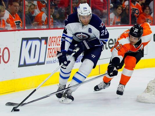Winnipeg Jets' Blake Wheeler (26), left, brings the puck around the back of the net followed by Philadelphia Flyers' Mark Streit (32) in the first period of an NHL hockey game, Thursday, Jan. 29, 2015, in Philadelphia. (AP Photo/Tom Mihalek)