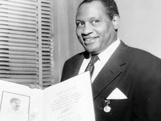 Paul Robeson, shown in 1953 displaying a bound citation for the International Stalin Peace Prize.