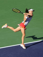Martina Hingis serves as her partner Hung-Jan Chan