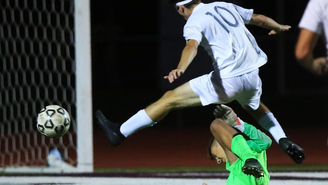 Augusta's Braydon Wilcox (10) jumps over Buhler's goal keeper Jax Frederick (0) during their game Tuesday evening in Buhler. Augusta defeated Buhler 5-0.