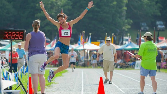 Annette Bednosky of Jefferson, NC, jumps for joy after winning the 2014 Grandfather Mountain Marathon. The race starts at 6:30 a.m. Saturday at Appalachian State University.